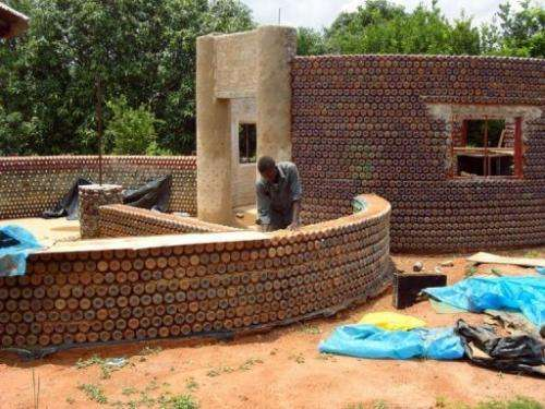 A man builds a wall with plastic bottles in the village of Sabon Yelwa