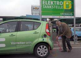 A man charges  his electric car at an electric filling station in Dresden