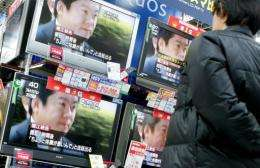 A man looks at a television news report on former Livedoor Co. President Takafumi Horie at an electronics shop in Tokyo