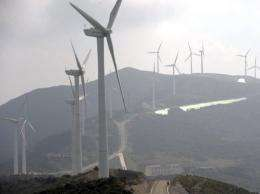 A man (lower) walks near a wind turbine complex on the Zhemo Mountain