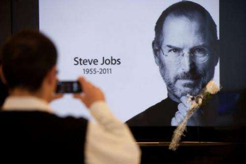 A man takes a picture of a portrait of Steve Jobs