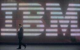 A man walks past the IBM logo