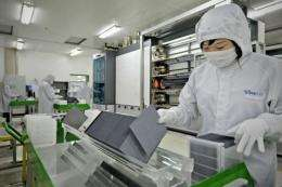 A masked worker sorts silicon wafers at the manufacturing centre of solar cell maker Trina Solar