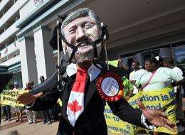 An activist wears a mask depicting the face of Canadian Prime Minister Stephen Harper during a protest in Durban