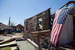 An American flag hangs off a destroyed house