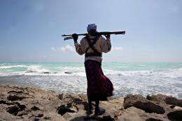 An armed Somali pirate stands along the coastline of Hobyo town in northeastern Somalia in 2010