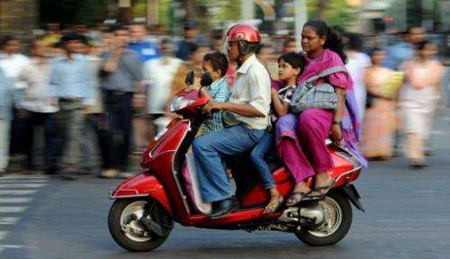 An Indian family travelling on a scooter in the commercial district of Fort in Mumbai