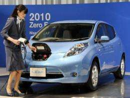 "A Nissan employee demonstrates how to plug in the ""Leaf"""