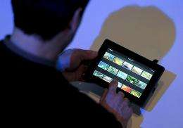 A participant looks at the new tablet by Blackberry, the 'Playbook,' at the 3GSM World congress
