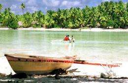 A traditional Micronesian canoe sits on the shore as people cross a lagoon on an atoll of Tarawa