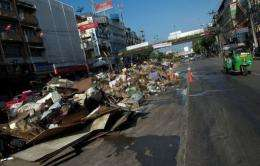 A vehicle drives past a garbage pile in a road in Bangkok following the floods
