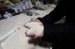 A vendor picks up rice at her stall in a market in Beijing