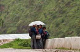 Bhutanese schoolgirls take shelter under an umbrella during heavy rainfall