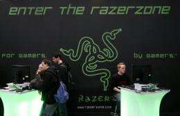 "Fairgoers play video games in front of the stand of gaming peripherals producer ""Razer"""