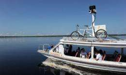 Google team members sail a boat with a 360-degree camera system mounted on a Trike on its top