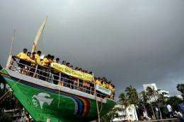 Indian children, representing a non-governmental organization in Mumbai, demonstrate on a Greenpeace boat