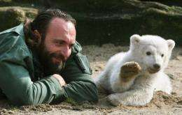 Knut, a three-month-old polar bear cub, appears to wave as he plays with his minder Thomas Doerflein in 2007