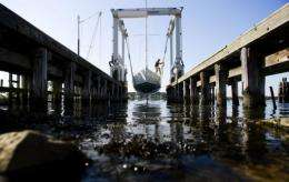 Land Crewman Christopher Bird pulls a sail boat out of the water