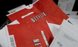 Netflix envelopes sit in a bin of mail at the U.S. Post Office sort center