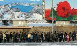 North Koreans wait for a bus under a poster of Mount Paekdu -- which erupted in 1903