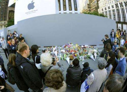 People gather around a makeshift memorial outside the Apple Flagship store