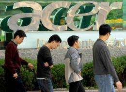 People walk past a logo of Acer in Shichih, Taipei