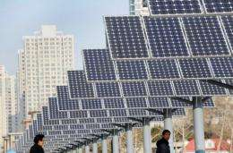 Residents walk past a line of solar power panels