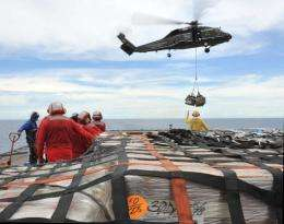 US sailors aboard the USS Blue Ridge move pallets of humanitarian relief supplies bound for Japan across the flight deck