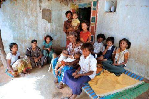 Vadthya Sukhya and Vadthya Achi with their eleven children in front of their home in Nalgonda District near Hyderabad