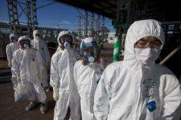 Workers in protective suits outside the emergency operation center at the Fukushima Daiichi nuclear power station