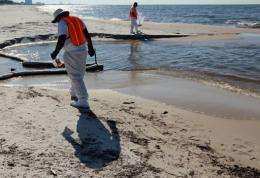 Workers look to clear off some of the oil residue on the beach from the Gulf of Mexico oil spill