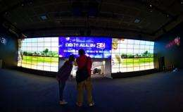 Workers put up a 3D videowall in the electronics giant LG's booth at the 51th edition of the IFA trade fair in Berlin