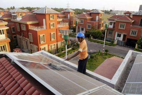 An Indian worker cleans solar panels fitted onto the roof of a residential house in Rabirashmi Abasan