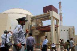 An Iranian security man stands next to journalists outside the Russian-built Bushehr nuclear power plant