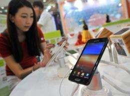 "A South Korean woman inspects Samsung's smartphone ""Galaxy Note"" during an IT show in Seoul"