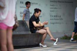 A woman looks at a smartphone in Beijing in May 2012