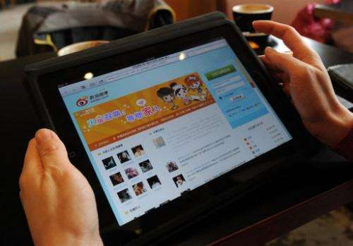 A woman views the Chinese social media website Weibo at a cafe in Beijing