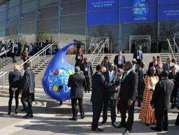 Participants talk next to logo of the 6th World Water Forum in Marseille