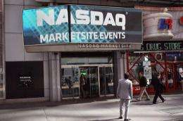 Pedestrians walk past the Nasdaq stock market at Times Square in New York City in March