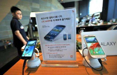 A man walks past a display of Samsung's Galaxy S3 at a mobile phone shop in Seoul in August 2012
