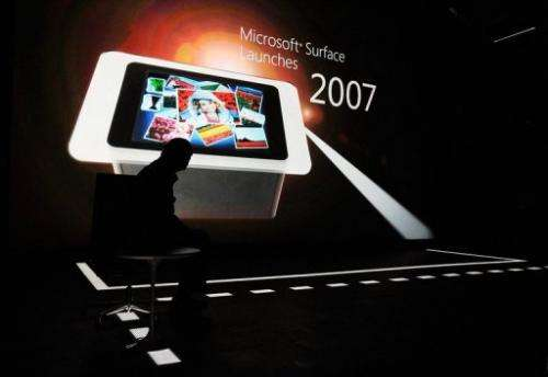 Microsoft CEO Steve Ballmer looks at a presentstion on a screen during unveiling of the new table Surface