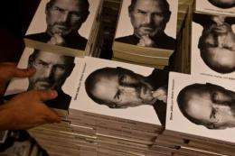 "A bookshop employee piles up copies of a biography of the late ""Apple"" co-founder Steve Jobs in 2011"