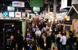 A crowd make its way between display booths along the aisles at the International Consumer Electronics Show in Las Vegas