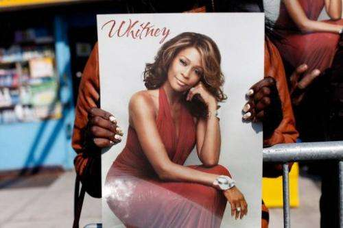 A fan holds a poster of Whitney Houston at the singer's February 18, 2012 funeral in Newark, New Jersey