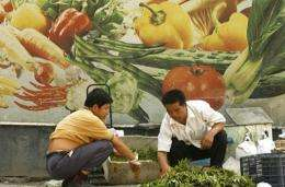 A farmer sorts out his produce at a vegetable market in Beijing