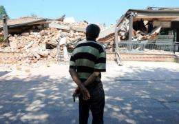 A man looks at damage after an earthquake in Cavezzo