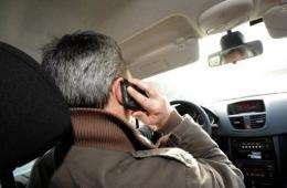 A man talks on a smartphone as he sits in a car in France, in January