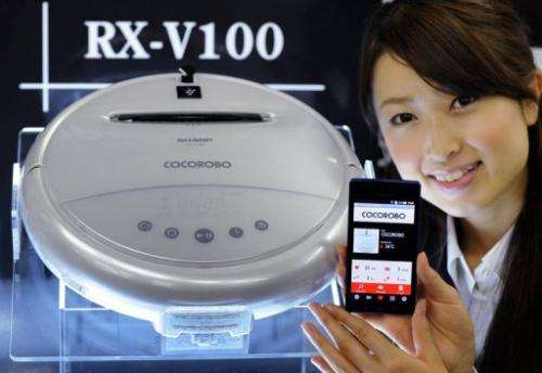 "A model displays Sharp's new ""Cocorobo"" talking robot vacuum cleaner in Tokyo"