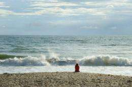 An early morning beach goer looks out over the Atlantic Ocean in Florida