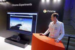 "An employee stands next to a giant screen for ""Chrome Experiments"""